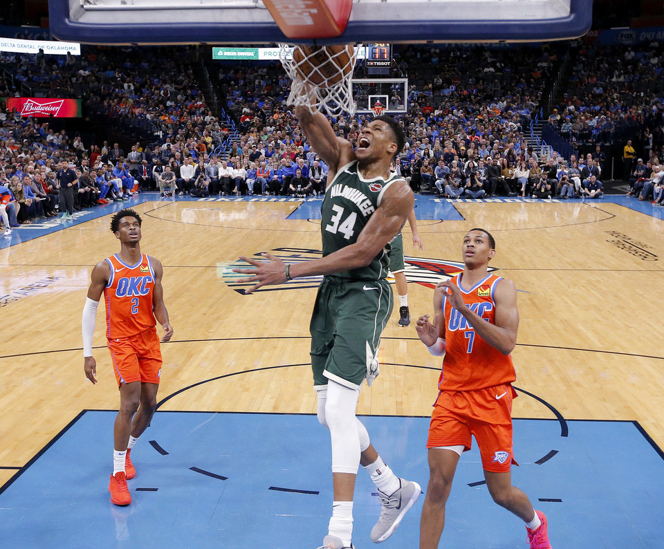 Photo - Milwaukee's Giannis Antetokounmpo (34) dunks the ball in in front of Oklahoma City's Shai Gilgeous-Alexander (2) and Darius Bazley (7) during the NBA game between the Oklahoma City Thunder and the Milwaukee Bucks at Chesapeake Energy Arena,   Sunday, Nov. 10, 2019.  [Sarah Phipps/The Oklahoman]