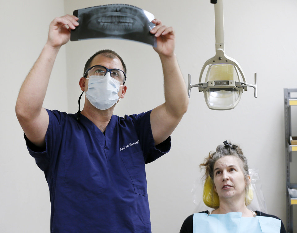 Photo -  Dr. Andrew Wheatley looks at an X-ray while patient Tabatha Wheeler looks on at the Open Wide Dental Clinic at Portland Avenue Baptist Church, 1301 N Portland Ave. [Photo by Nate Billings, The Oklahoman]