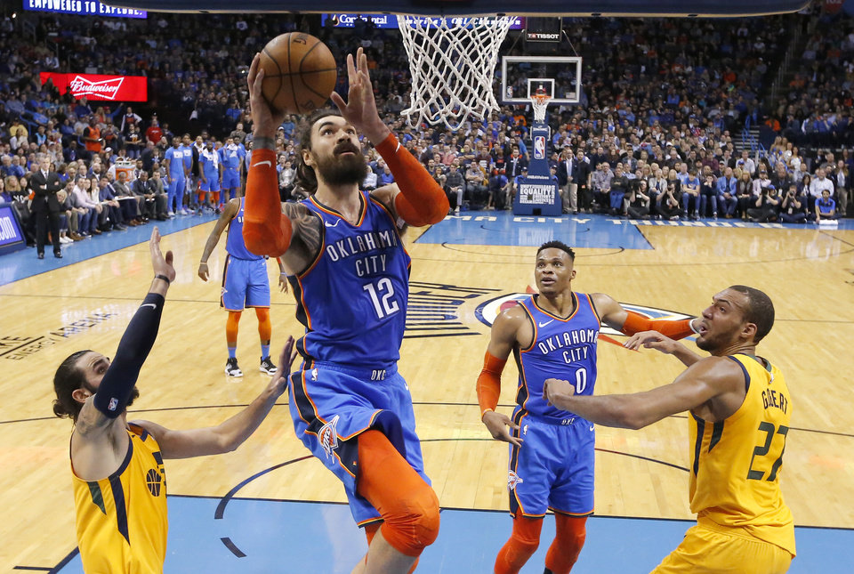Photo - Oklahoma City's Steven Adams (12) goes up for a basket as Utah's Ricky Rubio (3) and Utah's Rudy Gobert (27) defend during the NBA game between the Oklahoma City Thunder and the Utah Jazz at the Chesapeake Energy Arena, Friday, Feb. 22, 2019. Photo by Sarah Phipps, The Oklahoman