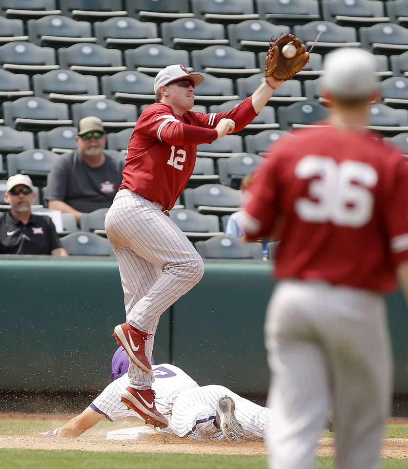 Photo - Oklahoma's Brylie Ware leaps for the ball as TCU's Conner Shepherd slides to third in the fourth inning during a Big 12 baseball tournament game between the University of Oklahoma (OU) and TCU at Chickasaw Bricktown Ballpark in Oklahoma City, Okla., Thursday, May 23, 2019.  [Bryan Terry/The Oklahoman]