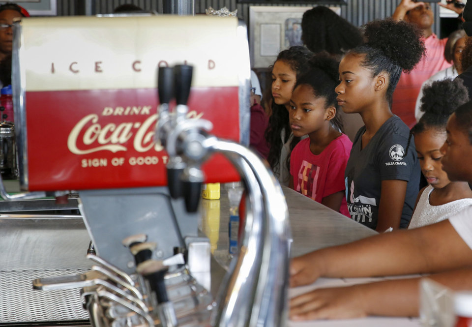 Photo - Children, including Victoria Turner, 16, middle, and Eve Wesley, 10, second from left, sit at the counter inside Kaiser's Grateful Bean Cafe to reenact the first Katz Drug Store sit-in, one of the first civil rights protests in the nation, in Oklahoma City, Saturday, Aug. 18, 2018. The sit-in was to commemorate the 60th anniversary of the Katz Drug Store sit-ins. The first Katz Drug Store sit-in happened on August 19, 1958. Photo by Nate Billings, The Oklahoman
