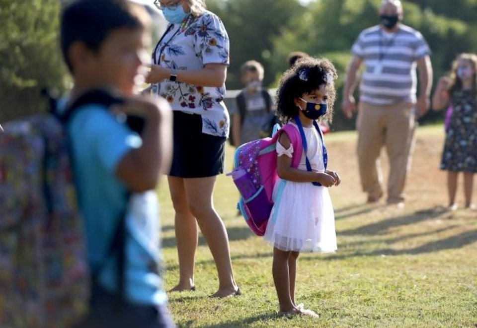 Photo -  Kindergartner Aubree Freeman, 6, waits in line after she was dropped for her first day of school at Charles Haskell Elementary School on Thursday. [Bryan Terry/The Oklahoman]
