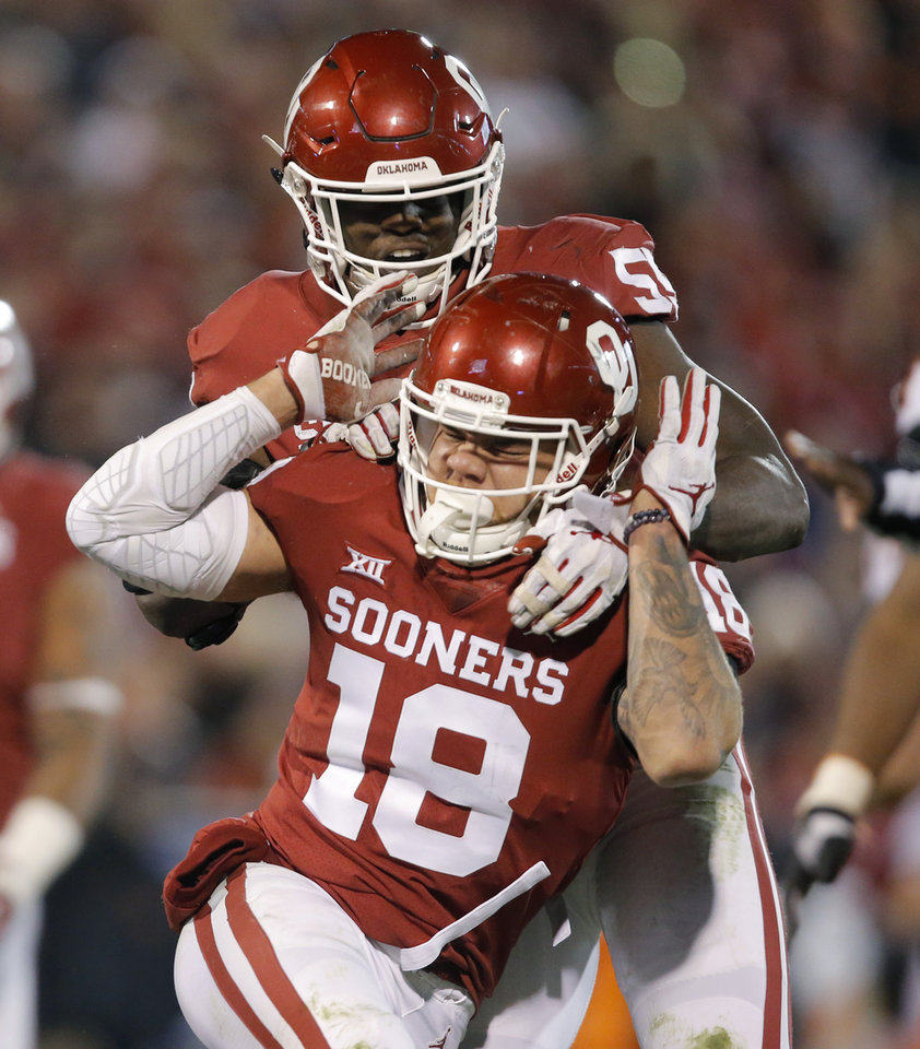 Photo - Oklahoma's Curtis Bolton (18) and Kenneth Mann (55) celebrate after a stop during a Bedlam college football game between the University of Oklahoma Sooners (OU) and the Oklahoma State University Cowboys (OSU) at Gaylord Family-Oklahoma Memorial Stadium in Norman, Okla., Nov. 10, 2018.  Photo by Bryan Terry, The Oklahoman