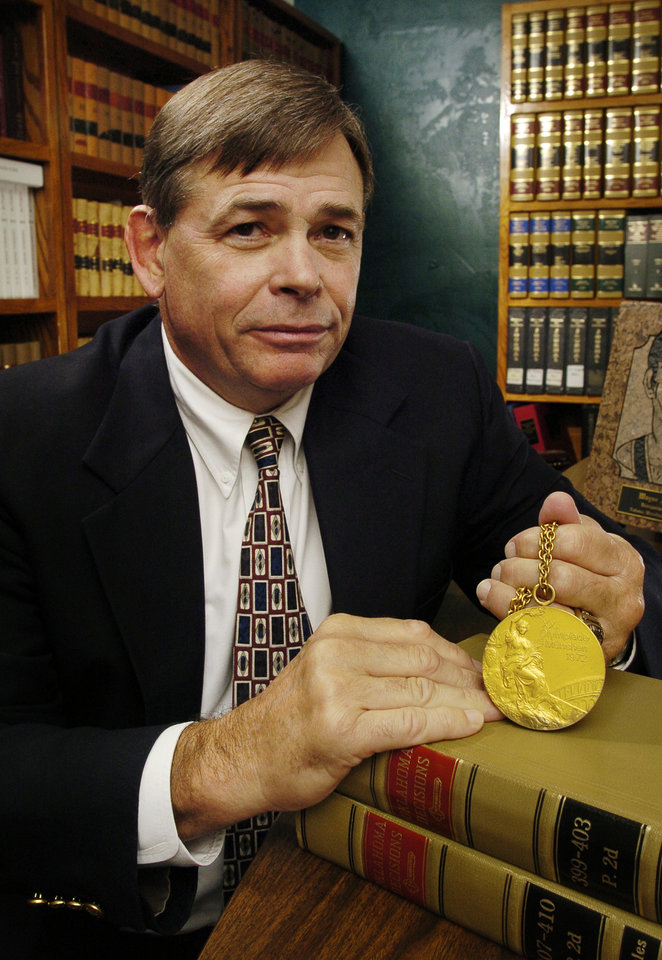 Photo - EDMOND, OK;  THURSDAY AUGUST 19, 2004.   1972 Olympic gold medal winner and Edmond lawyer Wayne Wells in his law office in Edmond.  Staff Photo by Steve Sisney