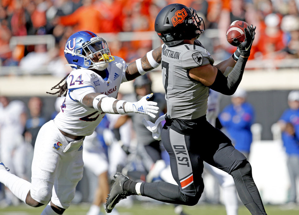 Photo - Oklahoma State's Dillon Stoner (17) catches a ball for a touchdown as Kansas's Ricky Thomas (24) defends during the college football game between the Oklahoma State University Cowboys and the Kansas Jayhawks at Boone Pickens Stadium in Stillwater, Okla., Saturday, Nov. 16, 2019.  [Sarah Phipps/The Oklahoman]