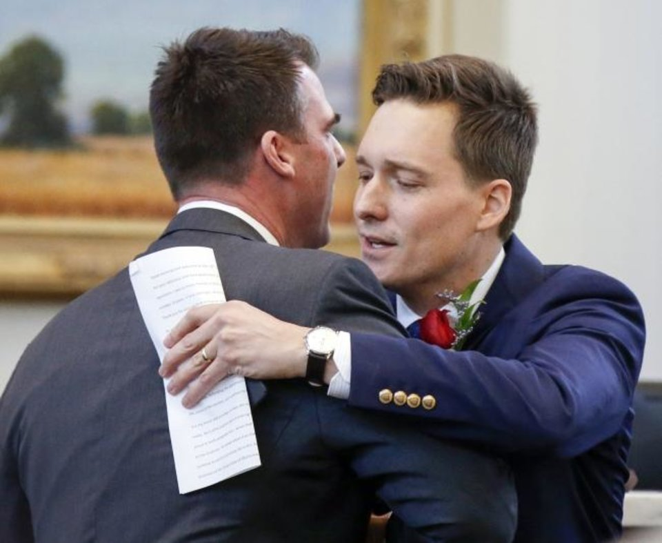 Photo -  Gov. Kevin Stitt, left, hugs Lt. Gov. Matt Pinnell after Pinnell spoke and introduced Stitt in the House of Representatives chamber during Rose Day. [Nate Billings/The Oklahoman]