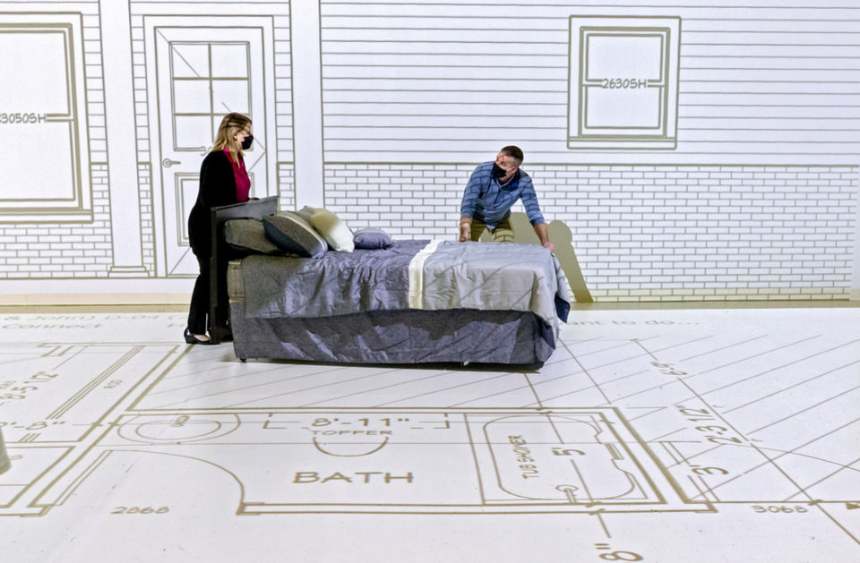 Photo -  Projected Plans owners Brian and Angela Porch prepare a projection of a life-size blueprint for a client to experience the layout of a new home at Projected Plans in Norman. [CHRIS LANDSBERGER photos/THE OKLAHOMAN]
