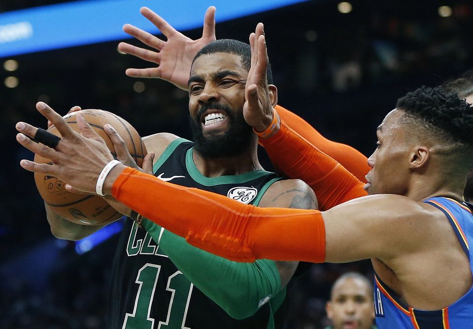 Photo - Oklahoma City Thunder's Russell Westbrook, right, defends against Boston Celtics' Kyrie Irving, left, during the first half of an NBA basketball game in Boston, Sunday, Feb. 3, 2019. (AP Photo/Michael Dwyer)