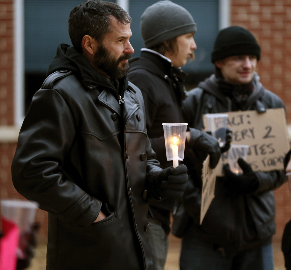 Photo - Xavier McClure, of Oklahoma City, holds a candle during a candlelight vigil outside the Board of Education meeting for Norman Public Schools at 131 S. Flood in Norman, Okla., Monday, Dec. 1, 2014. The vigil was in response to sexual assaults and bullying at Norman High School. Photo by Nate Billings, The Oklahoman