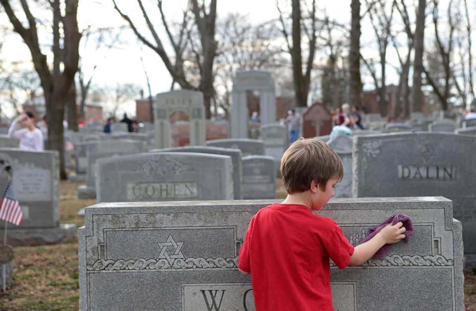 Photo - Theo Richmond, of University City, cleans a headstone at the Chesed Shel Emeth Cemetery in University City, Mo., on Wednesday, Feb. 22, 2017. Vice President Mike Pence and Governor Eric Greitens visited the cemetery after nearly over 150 headstones were toppled during the weekend. Hundreds of people came out to clean up after the repairs. (JB Forbes /St. Louis Post-Dispatch via AP)