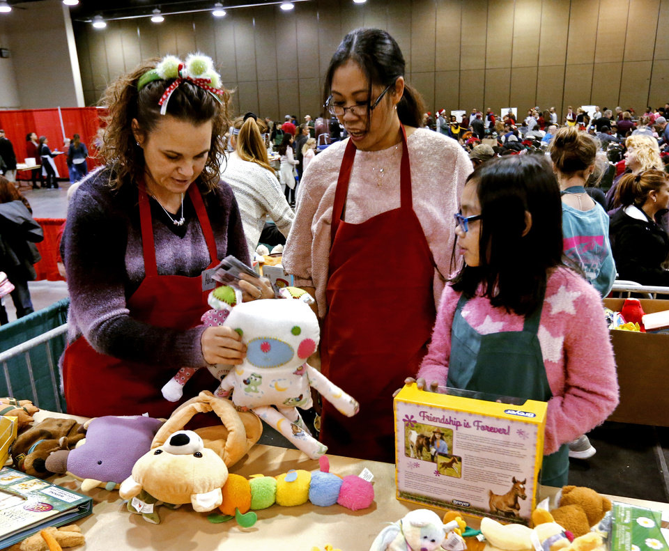 Photo -  Adrianne Ayers, of Midwest City, and mother and daughter Christine and Ann Marie Chapman, of Oklahoma City, gather toys to distribute to children during the dinner. Ann Marie donated her own presents, her mother said. [Photo by Steve Sisney, The Oklahoman]