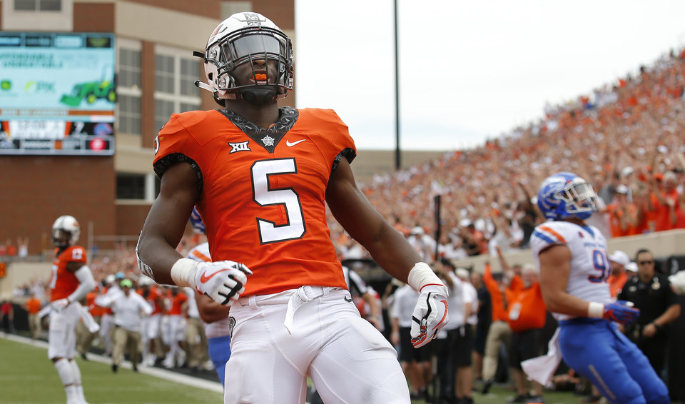 Photo - Oklahoma State's Justice Hill (5) celebrates a touchdown in the second quarter during a college football game between the Oklahoma State Cowboys (OSU) and the Boise State Broncos at Boone Pickens Stadium in Stillwater, Okla., Saturday, Sept. 15, 2018. Photo by Sarah Phipps, The Oklahoman