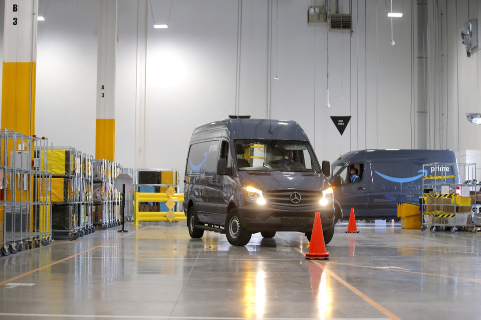 Photo -  Amazon delivery vans enter the new Amazon Delivery Center.
