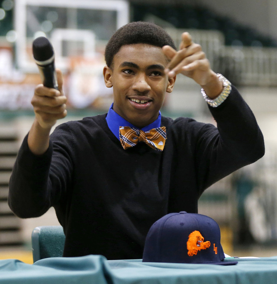 Photo - Jordan Sweat points to his fellow students during a national signing day ceremony at Edmond Santa Fe High School in Edmond, Okla., Wednesday, Feb. 4, 2015. Sweat signed to play football at Langston. Photo by Nate Billings, The Oklahoman