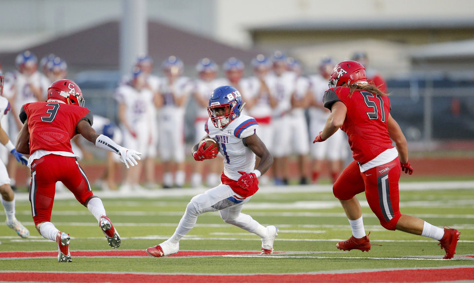 Photo - Bixby's Braylin Presley rushes in between Carl Albert defenders Cobe Crews (3)  and Nathan Mooney (51) during the high school football game between Bixby and Carl Albert at Carl Albert High School in Midwest City, Okla., Friday, Oct. 2, 2020. Photo by Sarah Phipps, The Oklahoman