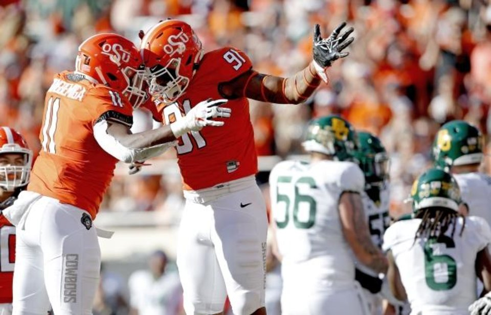 Photo -  Oklahoma State's Mike Scott, right, celebrates his sack on Baylor's Charlie Brewer with Amen Ogbongbemiga earlier this season. [Sarah Phipps/The Oklahoman]