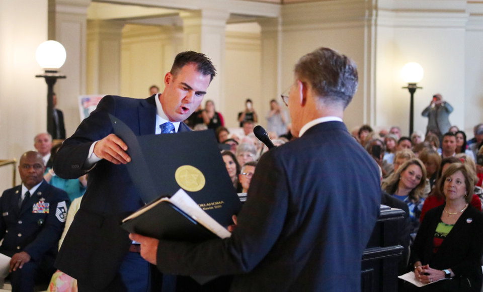 Photo - Gov. Kevin Stitt presents Mike Jestes, Chairman-Oklahoma National Day of Prayer Task Force, a proclamation during Oklahoma's National Day of Prayer service at the Capitol, Thursday, May 1, 2019. [Doug Hoke/The Oklahoman]