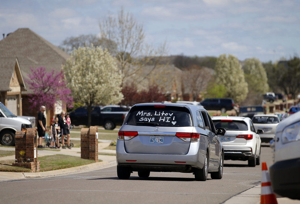 Photo - Families wave as an Oakridge Elementary faculty caravan drives through their neighborhood around the Moore school, Tuesday, March 24, 2020. [Bryan Terry/The Oklahoman]