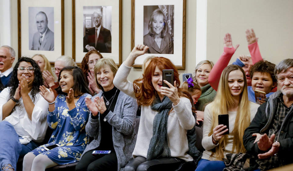 Photo -  Families and friends of inmates cheer as Gov. Mary Fallin signs commutations for 21 inmates Wednesday during a news conference at the state Capitol. In the center is Christie Luther, executive director of R.I.S.E., a program that  mentors and ministers to women in prison. [Photo by Jim Beckel, The Oklahoman]