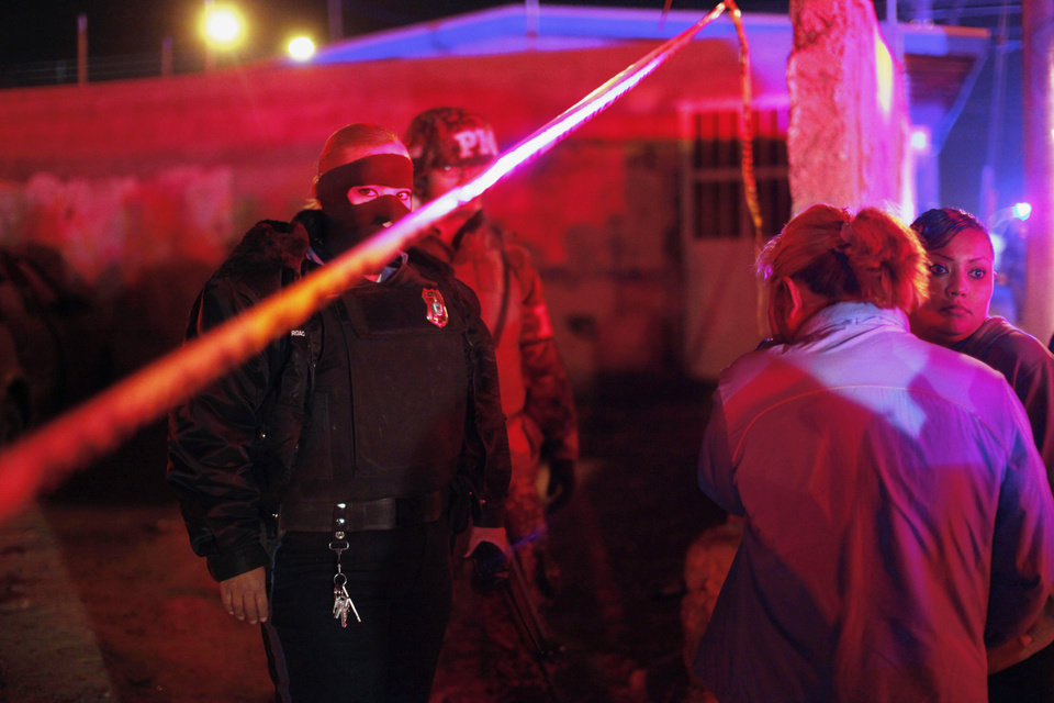 Photo - Residents wait for news on the periphery of a crime scene in this Nov. 19 photo, while a police officer and a soldier stand guard in Ciudad Juarez, Mexico. Two women and one man were killed by gunmen at a bar, police said. AP Photo