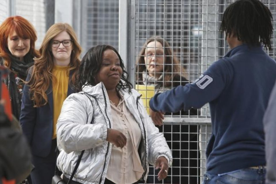 Photo -  Tondalao Hall, center, is greeted by family members Friday following her release from Mabel Bassett Correctional Center in McLoud. [Sue Ogrocki/The Associated Press]