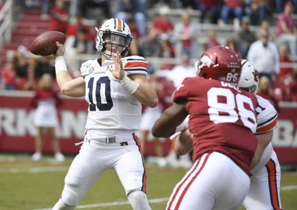 Photo - Auburn quarterback Bo Nix throws a pass against Arkansas during the first half of an NCAA college football game, Saturday, Oct. 19, 2019 in Fayetteville, Ark. (AP Photo/Michael Woods)