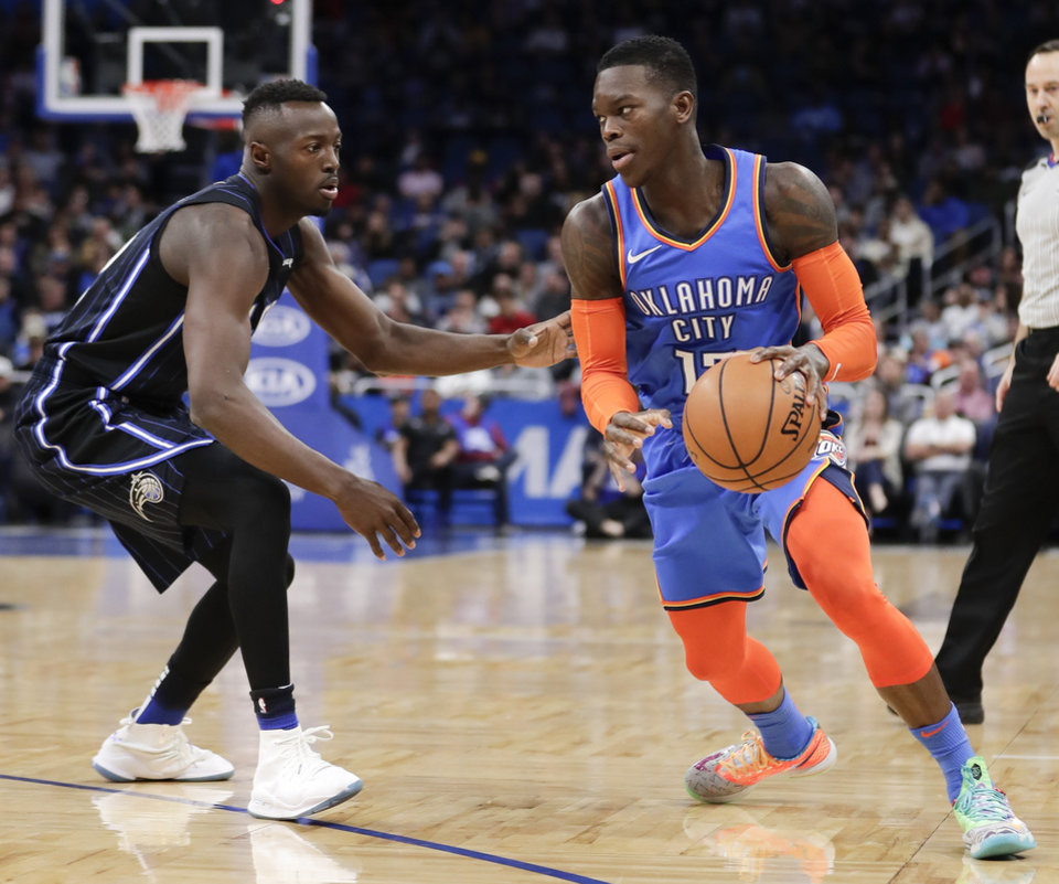 Photo - Oklahoma City Thunder's Dennis Schroder, right, looks for a way past Orlando Magic's Jerian Grant during the first half of an NBA basketball game, Tuesday, Jan. 29, 2019, in Orlando, Fla. (AP Photo/John Raoux)