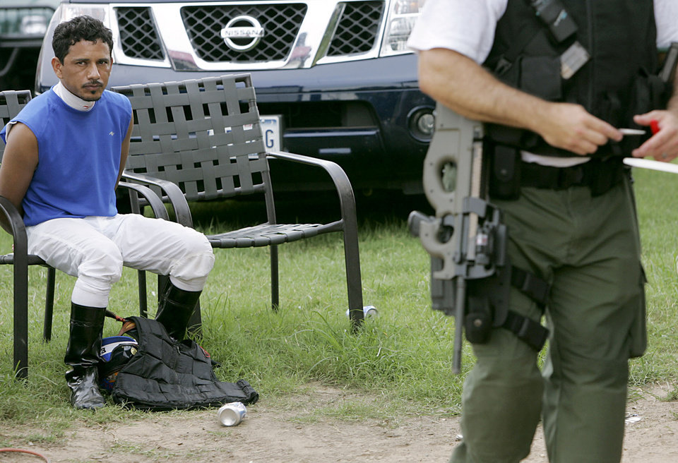 Photo - With his hands tied behind him, a jockey at the Red River Playgrounds, waits to be processed by law enforcement officials during a raid on a suspected illegal horse racing operation near Thackerville, OK., on Sunday, July 29, 2007. By John Clanton, The Oklahoman