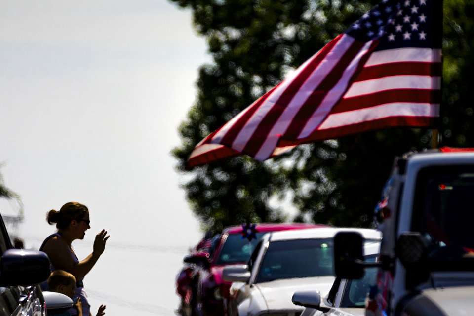 Photo - Spectators wave to participants as they drive by during the Bethany Freedom Festival parade in Bethany, Okla. on Thursday, July 4, 2019.    [Chris Landsberger/The Oklahoman]