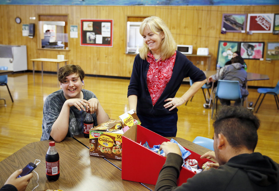 Photo - Principal Elizabeth Ressel talks to Robert Lash, 16, of Comanche, and other students as she hands out snacks during break time at FAME Academy, an alternative school in Comanche Public Schools, in Meridian, Okla., Wednesday, Oct. 3, 2018. Photo by Nate Billings, The Oklahoman