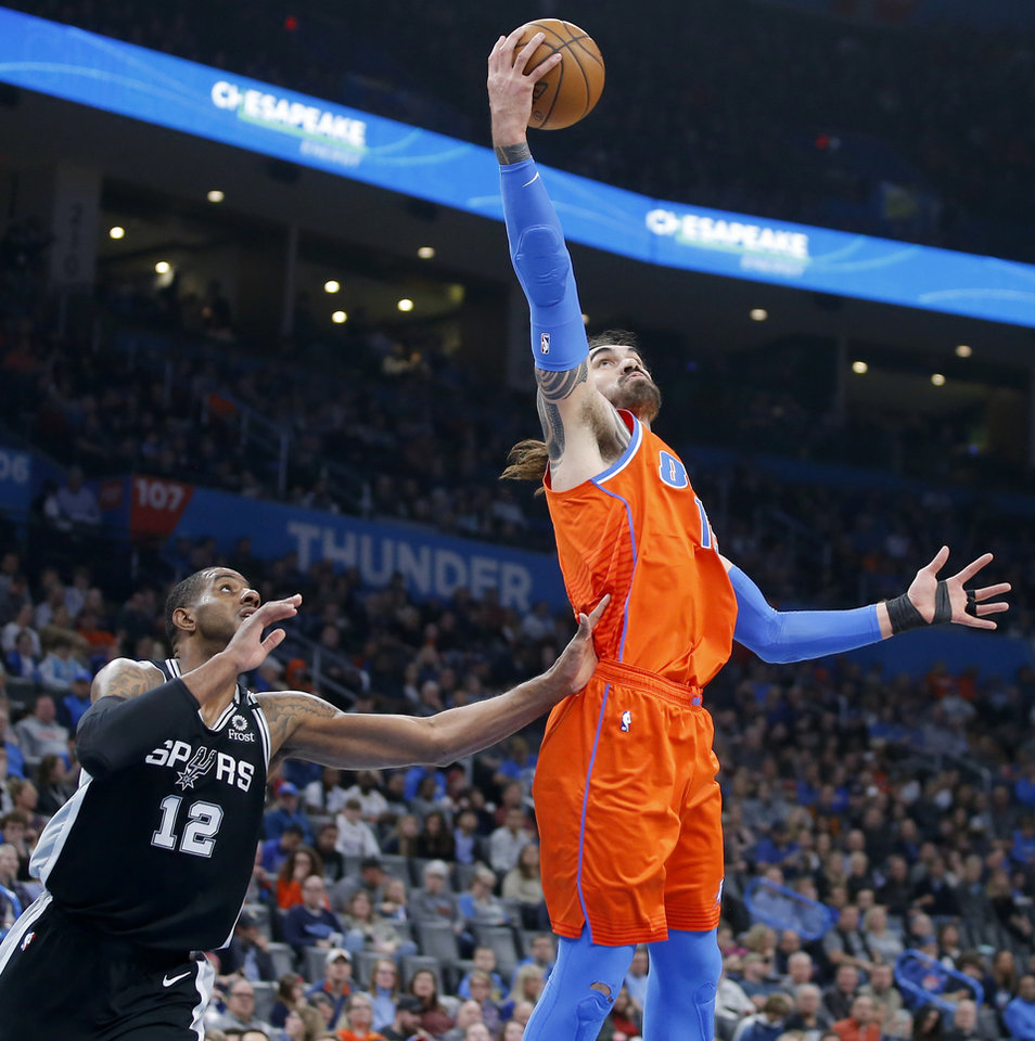 Photo - Oklahoma City's Steven Adams (12) catches the ball over San Antonio's LaMarcus Aldridge (12) during an NBA basketball game between the Oklahoma City Thunder and the San Antonio Spurs at Chesapeake Energy Arena in Oklahoma City, Sunday, Feb. 23, 2020. [Bryan Terry/The Oklahoman]
