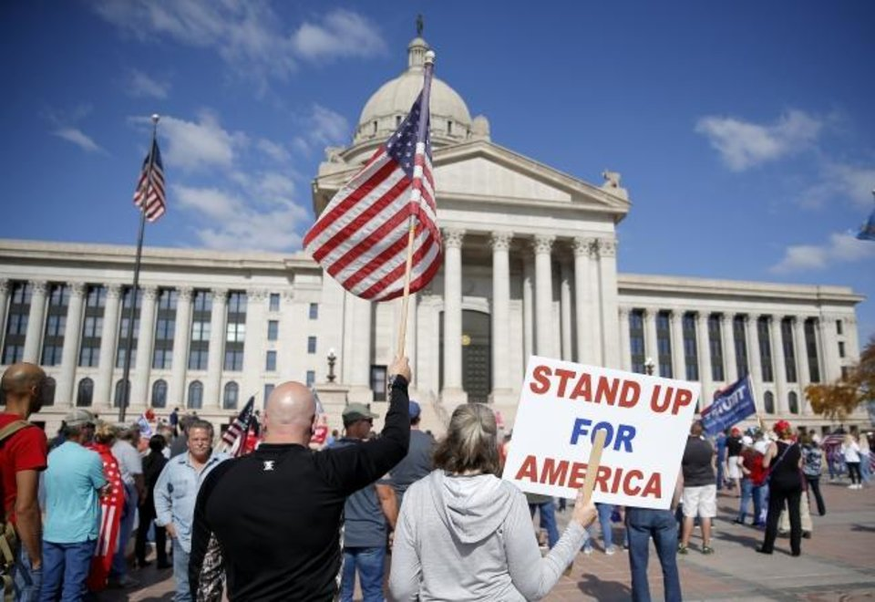 Photo -  Flags and signs are on display during Saturday's rally for President Donald Trump at the state Capitol in Oklahoma City. [Sarah Phipps/The Oklahoman]