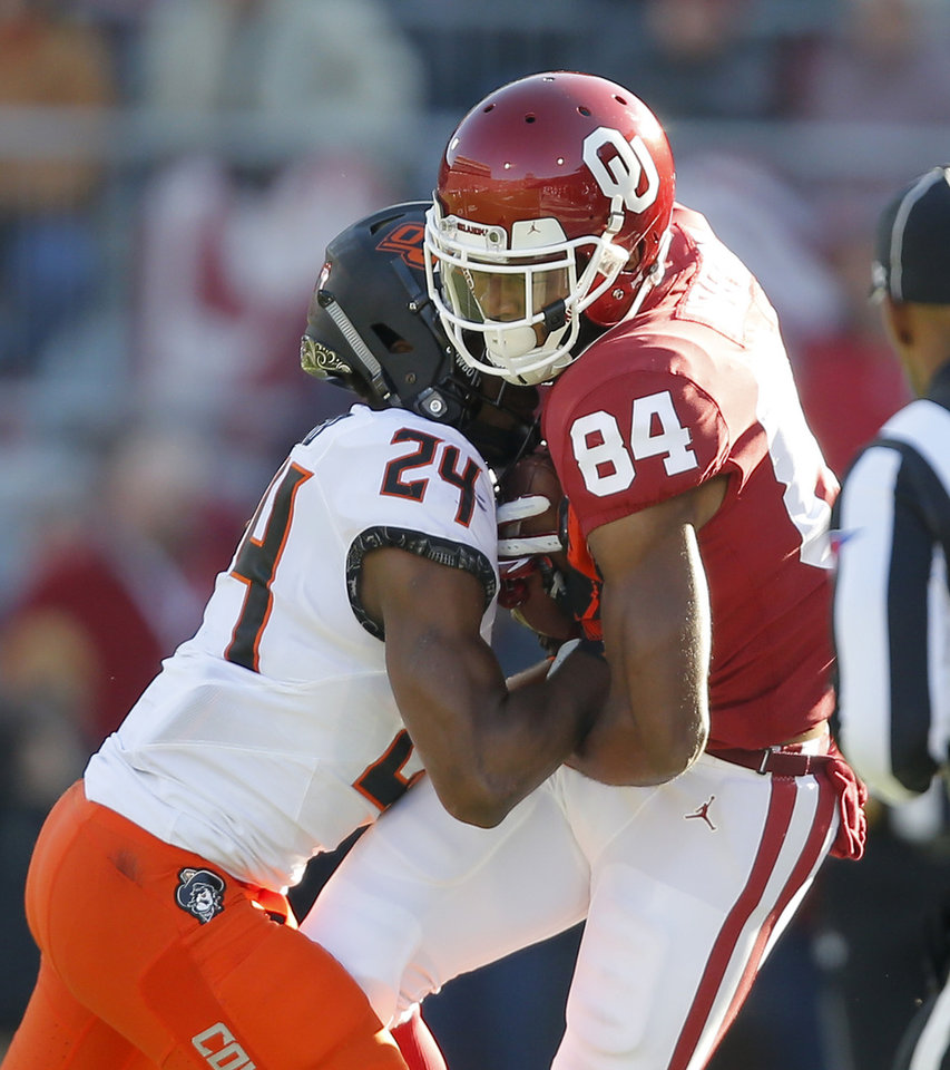 Photo - Oklahoma's Lee Morris (84) is pushed out by Oklahoma State's Jarrick Bernard (24) during a Bedlam college football game between the University of Oklahoma Sooners (OU) and the Oklahoma State University Cowboys (OSU) at Gaylord Family-Oklahoma Memorial Stadium in Norman, Okla., Nov. 10, 2018.  Photo by Bryan Terry, The Oklahoman