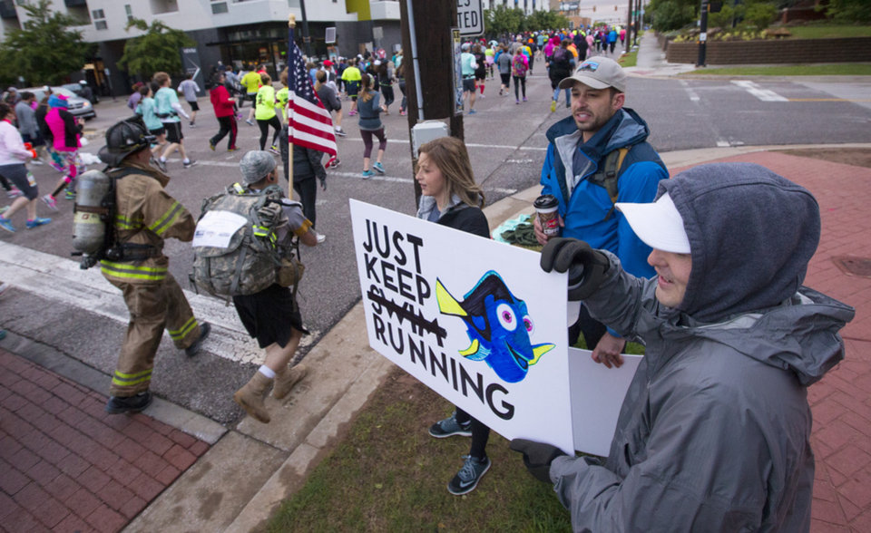Photo - Dickson Howell, right, holds a sign next to Paul Lewis and Sara Lewis as they encourage runners at NE 2 and Walnut Ave. during the Oklahoma City Memorial Marathon in Oklahoma City, Sunday, April 30, 2017. Photo by Nate Billings, The Oklahoman