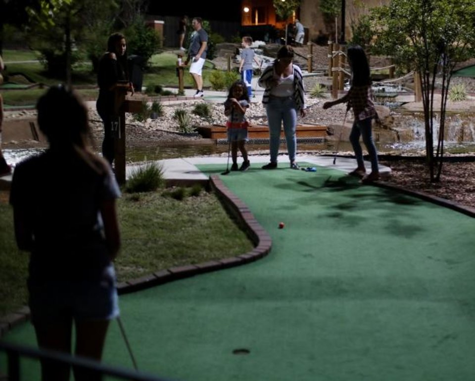 Photo -  The Brickopolis miniature golf course is a popular attraction along the Bricktown Canal on a summer evening. [Doug Hoke/The Oklahoman]