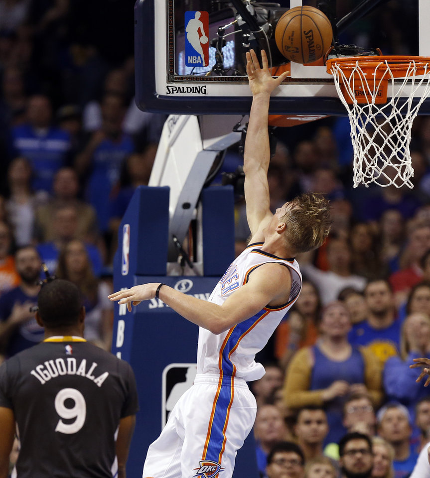 Photo - Oklahoma City's Kyle Singler (5) scores near Golden State's Andre Iguodala (9) during an NBA basketball game between the Oklahoma City Thunder and the Golden State Warriors at Chesapeake Energy Arena in Oklahoma City, Saturday, Feb. 27, 2016. Golden State won 121-118 in overtime. Photo by Nate Billings, The Oklahoman