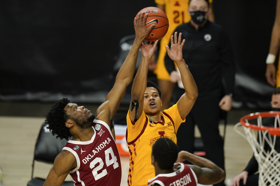 Photo - Oklahoma guard Elijah Harkless (24) blocks a shot by Iowa State guard Rasir Bolton during the second half of an NCAA college basketball game, Saturday, Feb. 20, 2021, in Ames, Iowa. (AP Photo/Charlie Neibergall)