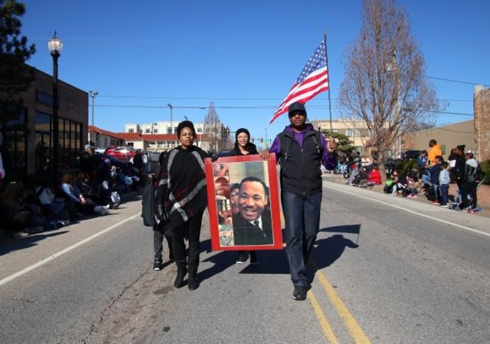 Photo -  People hold a poster of Martin Luther King Jr. while marching Monday in the Oklahoma City Martin Luther King Day Parade on Monday in downtown Oklahoma City. [Doug Hoke/The Oklahoman]