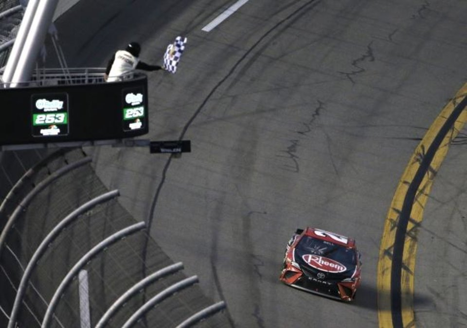 Photo -  Christopher Bell gets the checkered flag as he drives to the finish line during the NASCAR Cup Series road-course auto race at Daytona International Speedway, Sunday, Feb. 21, 2021, in Daytona Beach, Fla. (AP Photo/Terry Renna)
