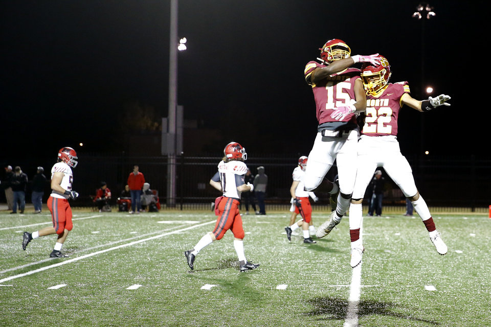 Photo - Putnam City North's Tyce Mythen, right, and Kayhon Russell celebrate after Mythen scored a touchdown after during a high school football game between Putnam City North and Mustang in Oklahoma City, Friday, Nov. 1, 2019.  [Bryan Terry/The Oklahoman]