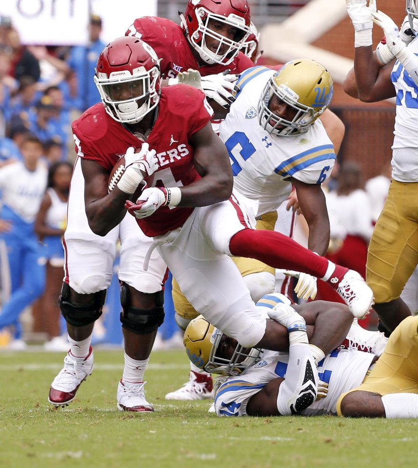 Photo - Oklahoma's Trey Sermon (4) leaps over UCLA's Krys Barnes (14) during a college football game between the University of Oklahoma Sooners (OU) and the UCLA Bruins at Gaylord Family-Oklahoma Memorial Stadium in Norman, Okla., on Saturday, Sept. 8, 2018. Photo by Steve Sisney, The Oklahoman