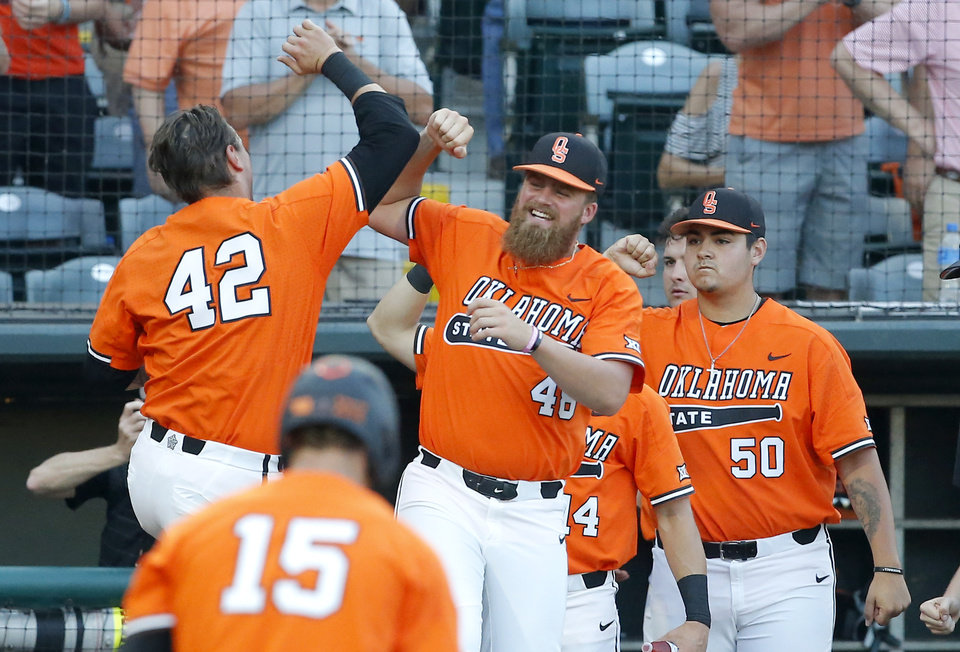 Photo - Oklahoma State celebrates a home run of Alix Garcia (42) in the 5th inning during the Oklahoma City Regional NCAA baseball game between Oklahoma State University (OSU) and UConn at Chickasaw Bricktown Ballpark in Oklahoma City,  Monday, June 3, 2019. [Sarah Phipps/The Oklahoman]