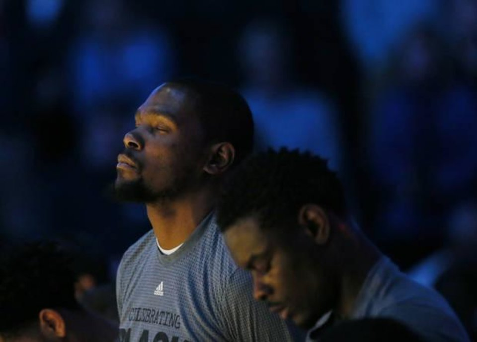 Photo - Oklahoma City's Kevin Durant (35), left, and Anthony Morrow (2) observe a moment of silence in memory of Ingrid Williams, the wife of Oklahoma City Thunder assistant coach Monty Williams, before an NBA basketball game between the New Orleans Pelicans and the Oklahoma City Thunder at Chesapeake Energy Arena in Oklahoma City, Thursday, Feb. 11, 2016. Ingrid Williams died Wednesday evening after being injured in a car crash Tuesday night. Photo by Nate Billings, The Oklahoman