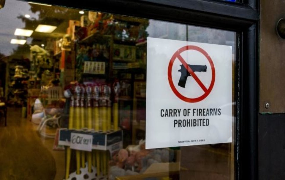 Photo -  A no firearms permitted sign is displayed on the front doors of the Learning Tree Toys, Books and Games in Oklahoma City. [Chris Landsberger/The Oklahoman]