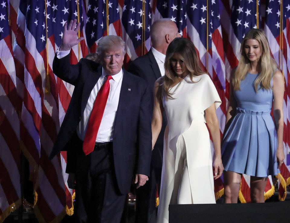 Photo - President-elect Donald Trump waves as he walks with his wife Melania Trump followed by his daughter Ivanka Trump after giving his acceptance speech during his election night rally, Wednesday, Nov. 9, 2016, in New York. (AP Photo/Mary Altaffer)