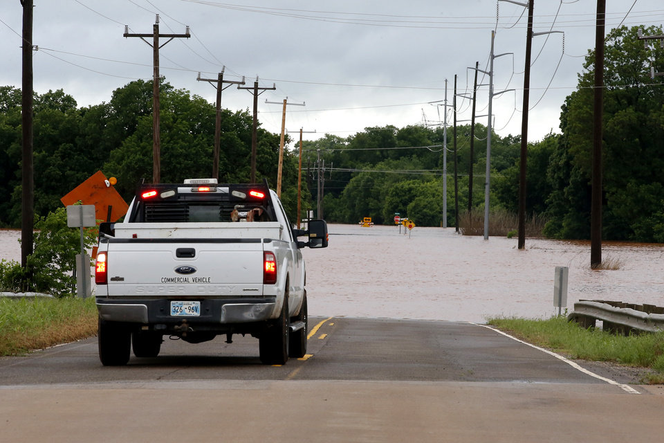 Photo - A truck stops in front of floodwater on NW 192 just west of Portland in Oklahoma City, Tuesday, May 21, 2019. [Bryan Terry/The Oklahoman]