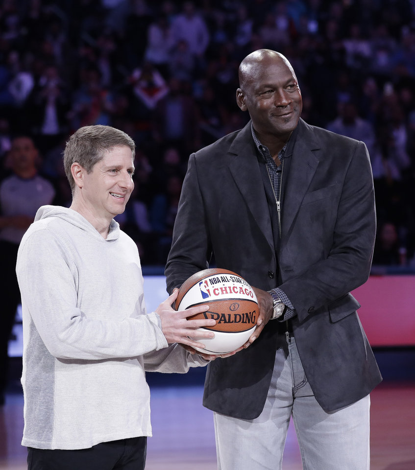 Photo - Michael Reinsdorf, president and COO, of the Chicago Bulls receives a basketball from Charlotte Hornets Owner Michael Jordan during the second half of an NBA All-Star basketball game, Sunday, Feb. 17, 2019, in Charlotte, N.C. The Team LeBron won 178-164. (AP Photo/Chuck Burton)