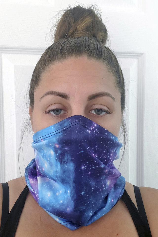 "Photo -  This June 23, 2020 photo provided by Kristen Kowall, 32, of Clearwater, Fla., shows her wearing a mask. In Florida, where many restaurants and bars reopened in early May, Kowall dined out with her fiance in early June. Like others in the restaurant, she didn't wear a mask. Later she tested positive for COVID-19. ""I just feel really groggy and tired. It hurts to walk. Especially my ankles and knees, it feels like my bones are going to fall apart,"" she said. ""I definitely would advise people from going out. It's not worth it."" (Kristen Kowall via AP)"