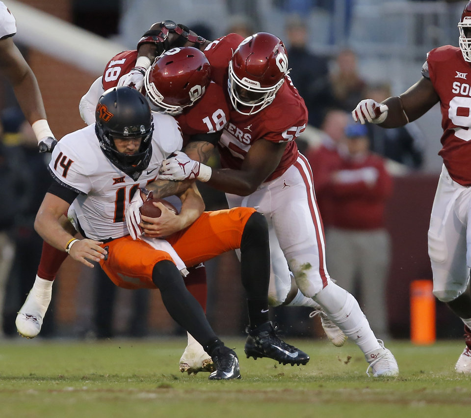 Photo - Oklahoma's Curtis Bolton (18) and Kenneth Mann (55) bring down Oklahoma State's Taylor Cornelius (14) for a loss during a Bedlam college football game between the University of Oklahoma Sooners (OU) and the Oklahoma State University Cowboys (OSU) at Gaylord Family-Oklahoma Memorial Stadium in Norman, Okla., Nov. 10, 2018.  Photo by Bryan Terry, The Oklahoman