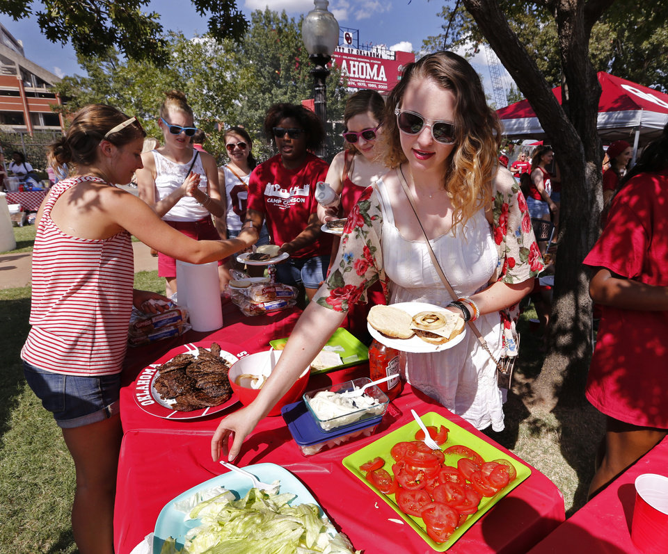Photo - Mady Masters gets a free burger from a tailgate table operated by a Christ Centered Campus Ministry before OU's game against Akron at Gaylord Family-Oklahoma Memorial Stadium in Norman on Sept. 5, 2015. Tailgating will be prohibited on OU's campus in 2020. [Photo by Steve Sisney, The Oklahoman]